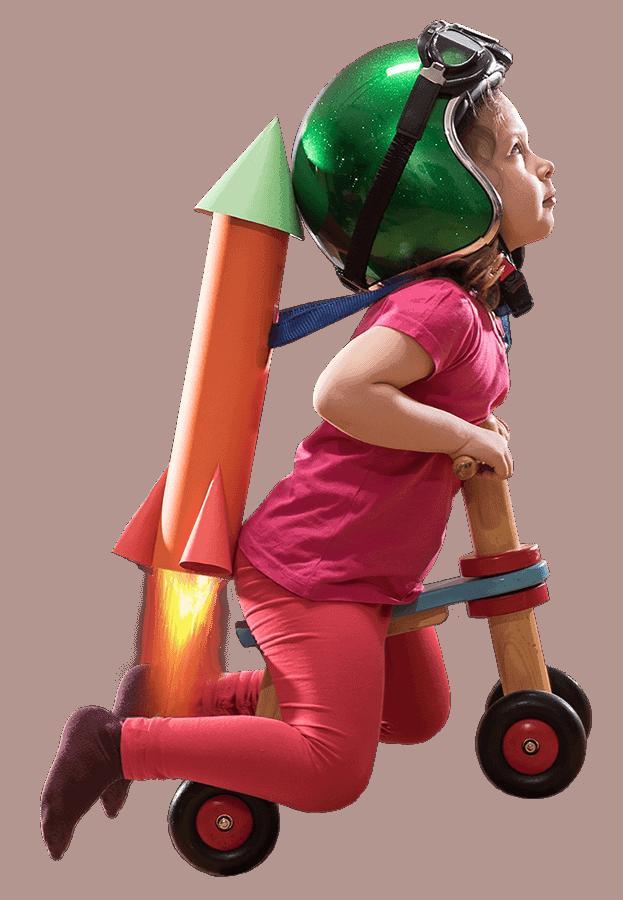 ילדה יושבת על אופניים ללא פדלים עם קסדה המסתכלת כלפי מעלה, עפה למעלה באמצעות טיל בצבע כתום